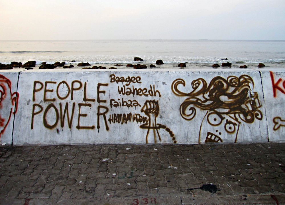 "In the aftermath of the coup, there was an explosion of street art and political messages graffitied onto the seawall surrounding the island of Malé. Translation: ""Traitor Waheed, go now."""