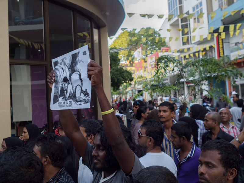 Protesters near Supreme Court hold up cartoons making fun of disgraced Justice Ali Hameed Photo: Aznym